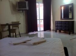 חדר מרווח עם מרפסת וטלויזיה - דירות נופש באילת